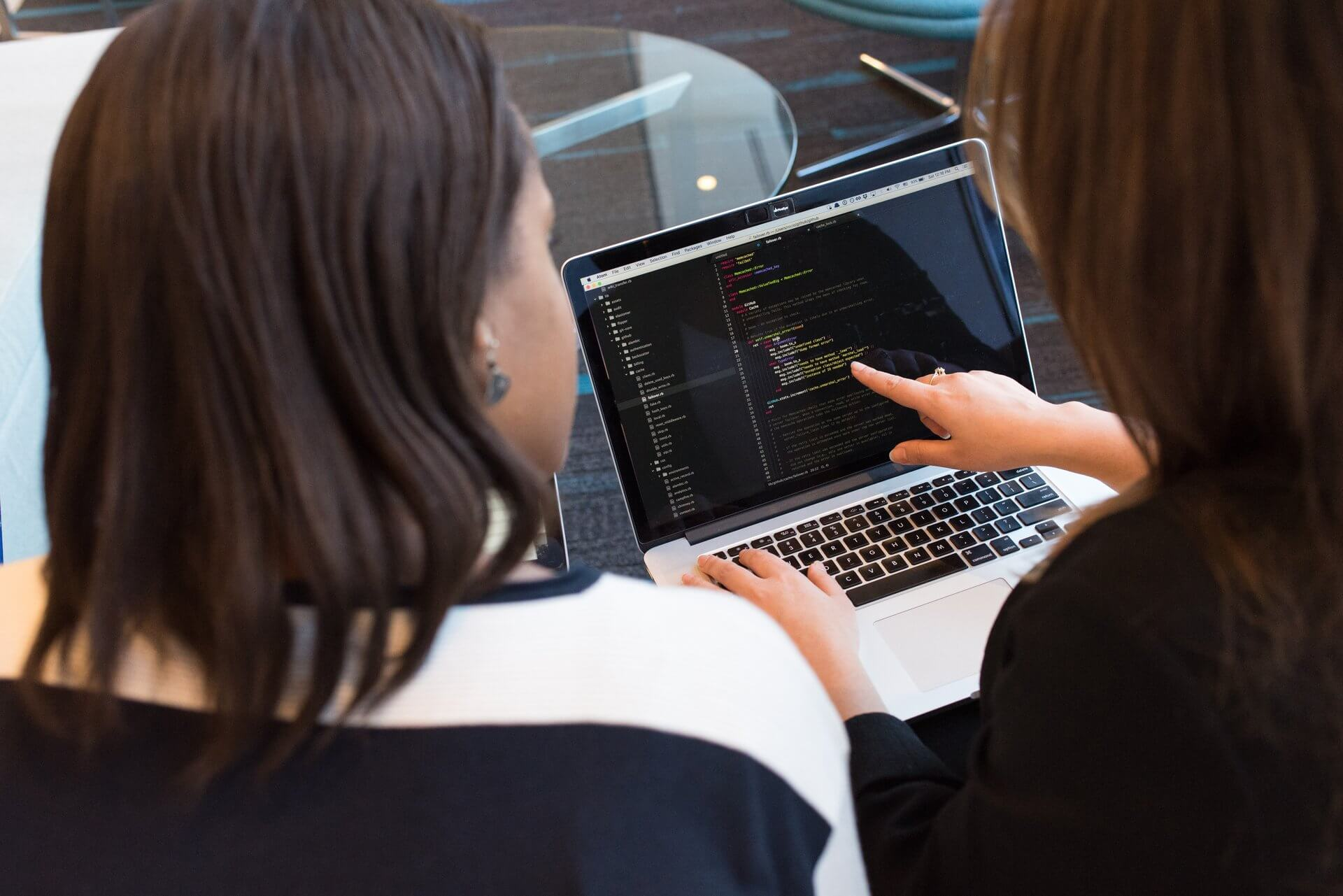 Two women looking at the code on a laptop